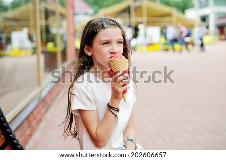 Cute brunette  kid  girl eating strawberry ice cream on the city street in summer day - stock photo