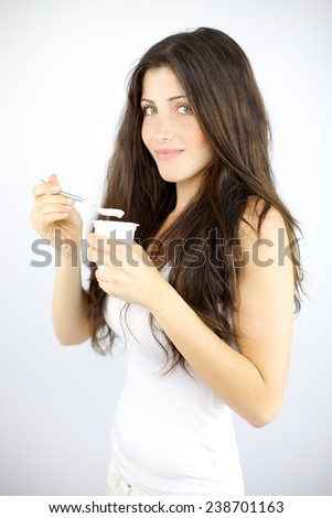Cute brunette with long hair eating white yogurt - stock photo