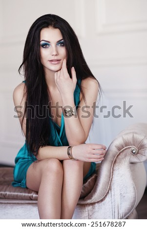 Cute brunette woman in gorgeous emerald dress. - stock photo