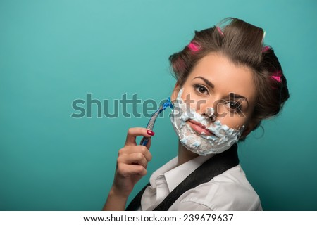 Cute brunette woman in hair curlers playing fool with foam on face shaving with razor, isolated on blue background, role gender reversal concept - stock photo