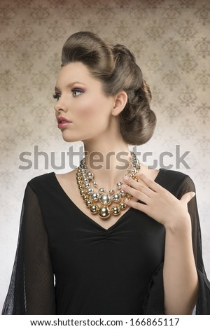 cute brunette woman posing with elegant hair-style, wearing pretty dark dress and big necklace in fashion portrait       - stock photo