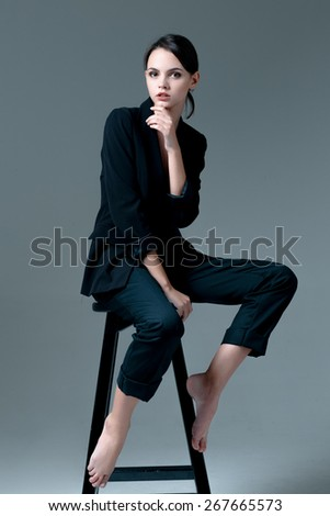 Cute brunette woman wearing a jacket over naked body sitting on the chair - stock photo