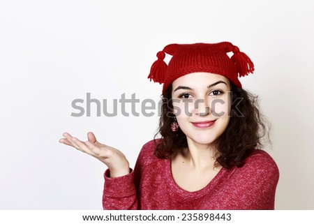Cute brunette woman with funny red hat expressing proposal - stock photo