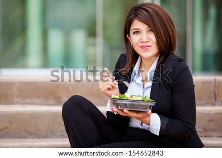 Cute business woman eating a healthy salad and relaxing outdoors - stock photo