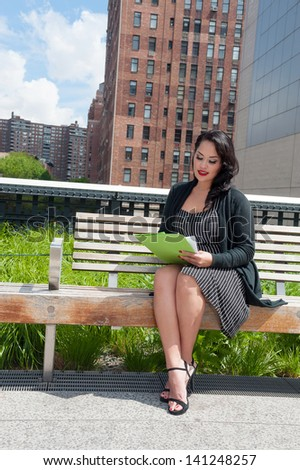 Cute business woman reading on High Line, NYC - stock photo