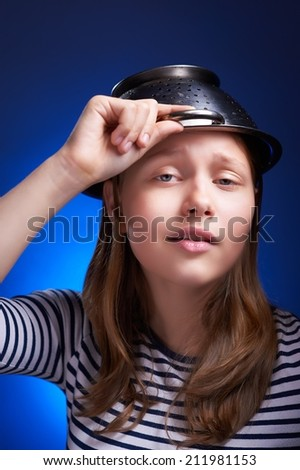 Cute calm teen girl with a colander on her head - stock photo