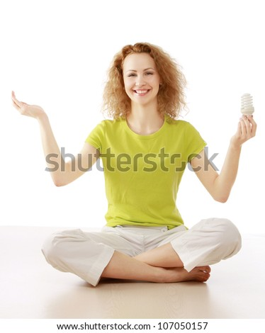 Cute casual female holding a light bulb over head - stock photo