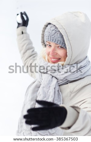 Cute casual young woman throwing snowball in winter time. - stock photo