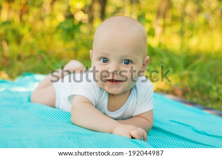 Cute caucasian baby boy in park looks at camera - stock photo