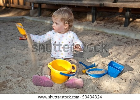 Cute Caucasian baby girl playing with the sand in sandpit. - stock photo