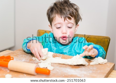 Cute caucasian baby making bread on a wooden table - stock photo