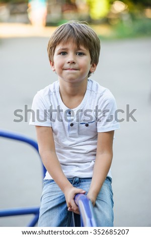 Cute  Caucasian  boy  playing on  playground outside in the summer sun. - stock photo