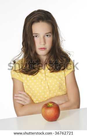 Cute Caucasian girl unhappy about eating an apple - stock photo