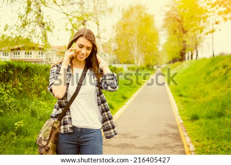 Cute Caucasian teenage girl in plaid shirt and jeans talking on the phone outdoors on summer or autumn day. - stock photo