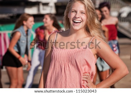 Cute Caucasian teenager with hand on hip laughing - stock photo