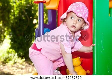 Cute caucasian toddler girl having fun playing on playground. - stock photo