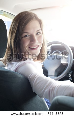 Cute caucasian woman indoor car holding steering wheel and turning to back seat - stock photo
