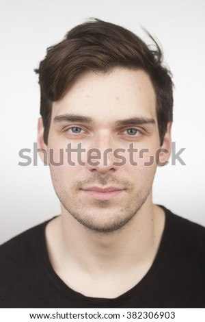 Cute caucasian young adult, in 20s, face close up portrait. White background. Almost no expression. Shallow depth of field. - stock photo