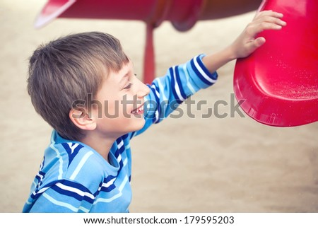 Cute cheerful boy playing on a colorful playground laughing happily - stock photo