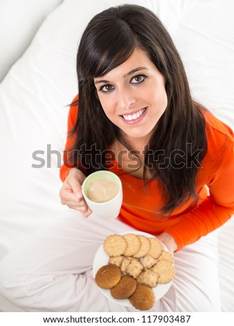 Cute cheerful brunette woman with breakfast sitting on white bed. She is holding a cup of steaming hot coffee and a plate of biscuits. - stock photo
