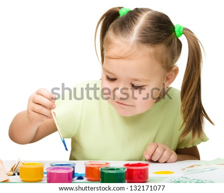 Cute cheerful child play with paints while sitting at table, isolated over white - stock photo