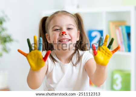 cute cheerful girl showing her painted hands in playroom - stock photo