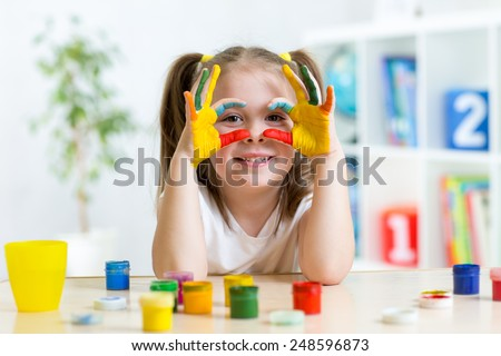 cute cheerful kid girl showing her hands painted in bright colors - stock photo