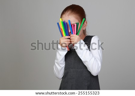 Cute cheerful little girl in school uniform holding a lot of of markers - stock photo