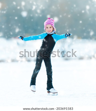 cute  cheerful little girl in thermal suits skating  outdoors - stock photo