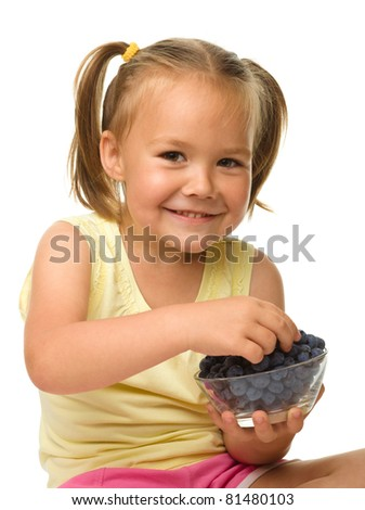 Cute cheerful little girl is eating blueberry, isolated over white - stock photo