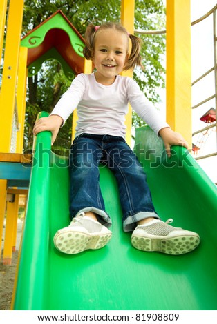 Cute cheerful little girl is playing on slider - stock photo
