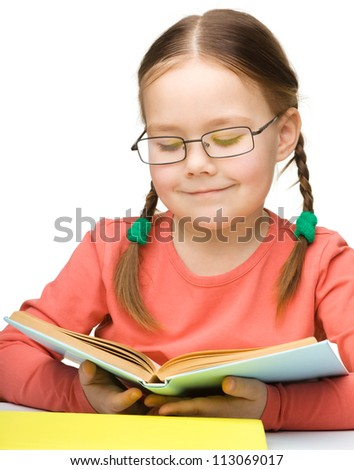Cute cheerful little girl reading book wearing glasses, isolated over white - stock photo