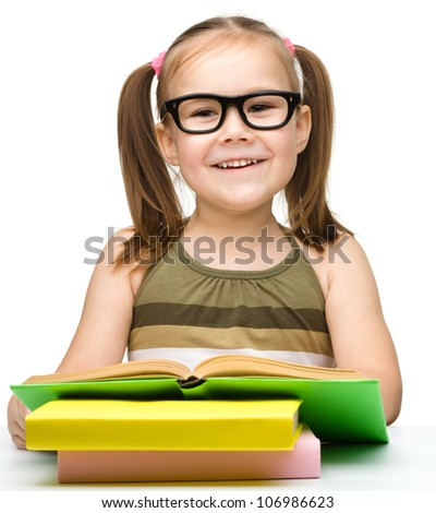 Cute cheerful little girl reading book while wearing glasses, isolated over white - stock photo