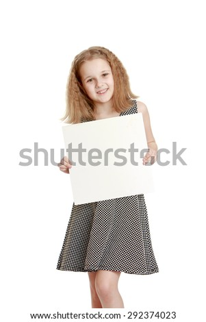 Cute cheerful teenage girl in a gray silk dress holds up a square or rectangular poster - isolated on white background - stock photo