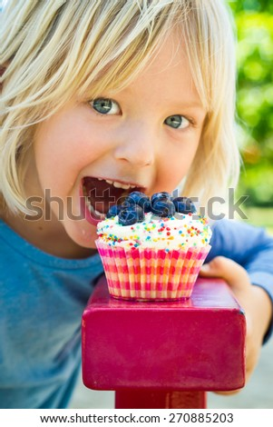 Cute child about to bite into a delicious cupcake. Cupcake is in focus. - stock photo