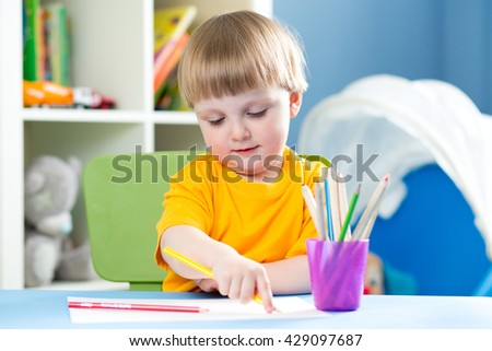 Cute child boy is drawing with color pencils in nursery - stock photo