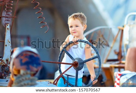 cute child boy pretends driving an imaginary car - stock photo