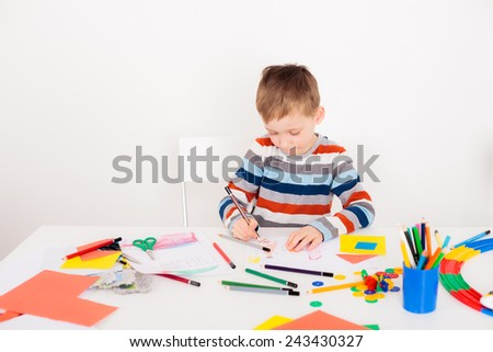 Cute child drawing picture at white table - stock photo