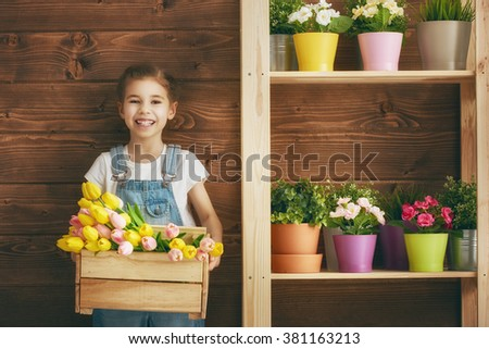 Cute child girl caring for her plants. Girl holding wooden box with tulips. Spring concept, nature and care. - stock photo