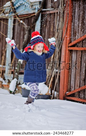 cute child girl having fun and running in winter snowy garden with wooden fence on background - stock photo