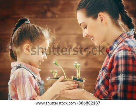 Cute child girl helps her mother to care for plants. Happy family engaged in gardening in the backyard. Mother and her daughter watch as a growing sprout. Spring concept, nature and care. - stock photo