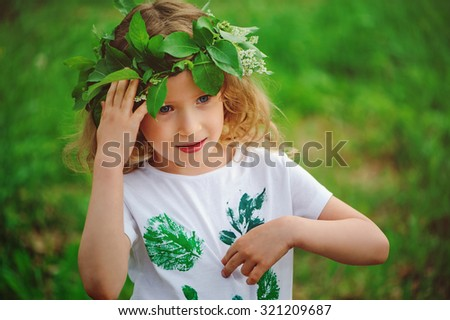 cute child girl in handmade forest wreath and craft shirt with leaf prints on the walk in summer - stock photo