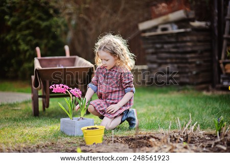 cute child girl in plaid dress planting flowers in spring garden with wheelbarrow on background - stock photo