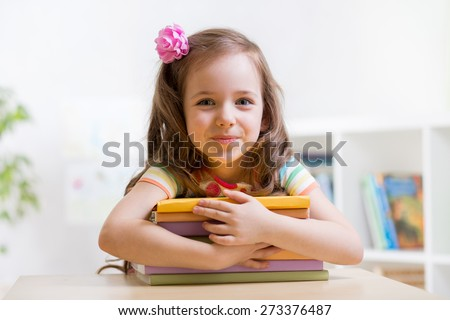 Cute child girl preschooler with books indoor - stock photo