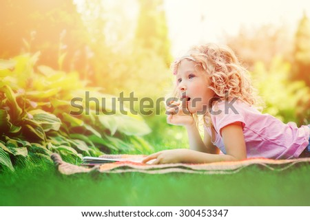 cute child girl reading book and dreaming in summer garden - stock photo
