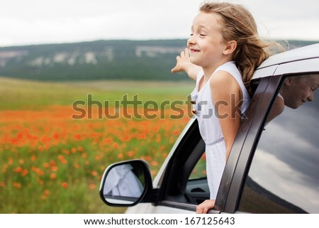 Cute child girl sitting inside a car on poppy field - stock photo