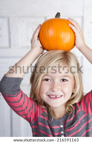 Cute child holding small pumpkin on her head - stock photo