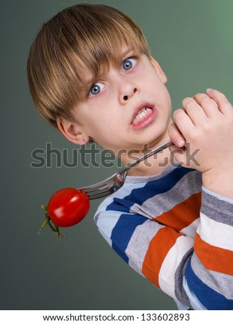 Cute child holding tomato on fork, hates vegetables - stock photo