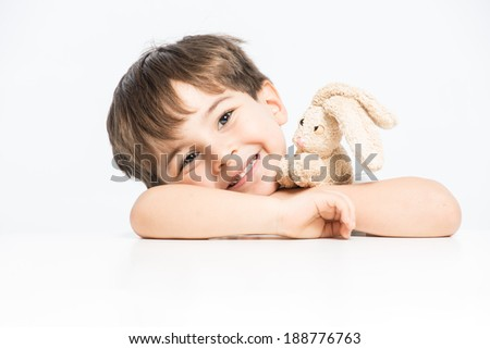 Cute child hugging his stuffed toy rabbit and smiling posing on white background half close-up - stock photo