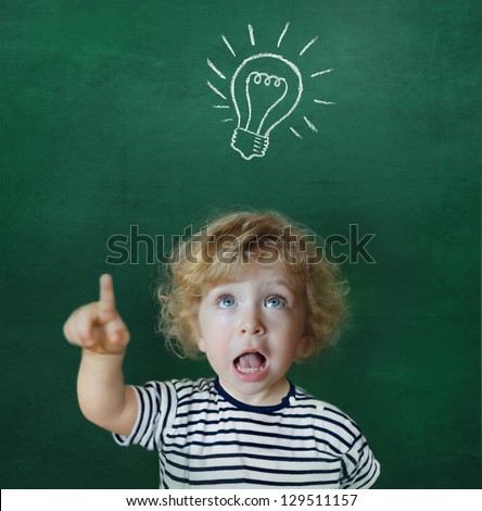 Cute child in front of a green chalkboard showing up to a light bulb - stock photo